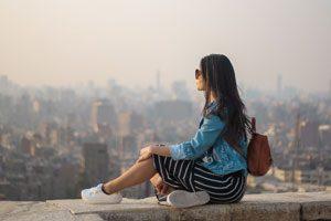 photo d'une femme admirant pensivement un paysage urbain